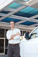 Handsome man standing besides car with arms crossed