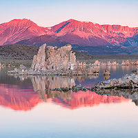 Rising sun illuminates Eastern Sierra mountains creating beautiful reflections on Mono Lake. Lee Vining, California