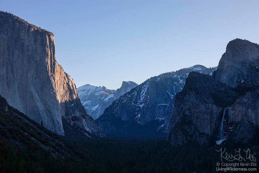 The sunrise lights up the eastern face of El Capitan, located in Yosemite National Park, California. Half Dome (center) and Bridalveil Fall (far right) are also visible in this view from Tunnel View.