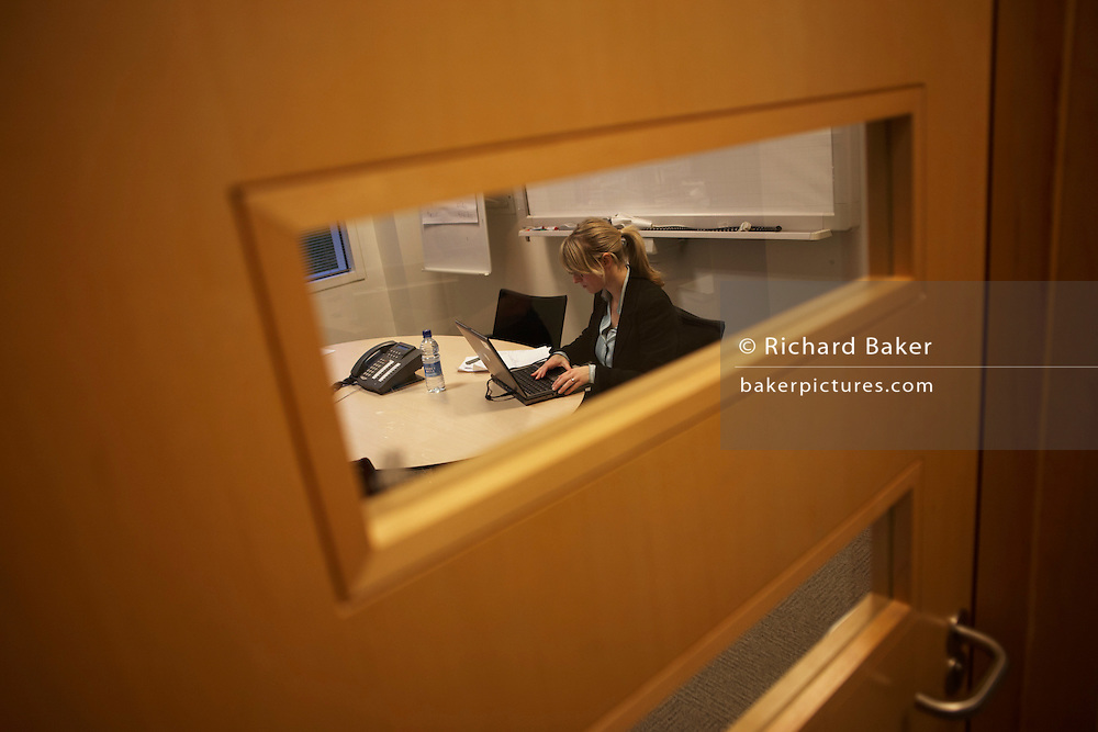 Working alone behind a closed door in a private workspace at the United Biscuits Group offices, Hayes London