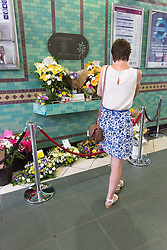 © Licensed to London News Pictures. 07/07/2015. London, UK. A woman looks at floral tributes shortly before observing a minute silence at Aldgate tube station in London, on the tenth anniversary, for victims of the 7/7 bombings. Photo credit : Vickie Flores/LNP