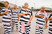 """17 JULY 2006 - PHOENIX, AZ: Inmates stand their hands over the hearts while the National Anthem is played in """"Tent City"""" in the Maricopa County Jail in Phoenix, AZ. There are about 650 inmates living in the tents. Maricopa County Sheriff Joe Arpaio recently started playing the Star Spangled Banner and God Bless America twice a day in the county jails. Inmates are encouraged, but not forced, to stand at attention with their hands over their hearts, when the music is played. When asked about the new policy Arpaio said, """"Our men and women are fighting and dying for our country in Iraq and that's the least these inmates can do."""" In 2011, the US Department of Justice issued a report highly critical of the Maricopa County Sheriff's Department and the jails. The DOJ said the Sheriff's Dept. engages in widespread discrimination against Latinos during traffic stops and immigration enforcement, violates the rights of Spanish speaking prisoners in the jails and retaliates against the Sheriff's political opponents.      PHOTO BY JACK KURTZ"""