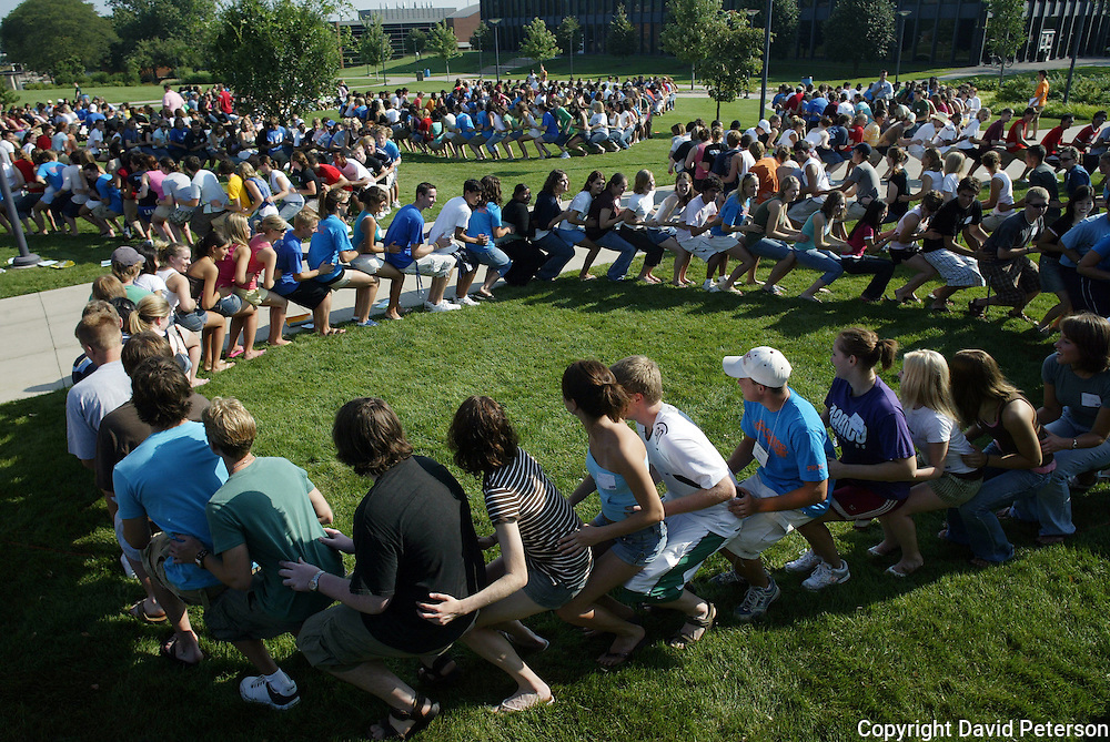 First year students at Drake University in Des Moines, Iowa, engage in a series of activities on campus to help them acclimate to college life and meet other freshmen.  Here they form a human chain, a show of unity. orientation,fun,meeting,circle,excitement,exercise,summer,freshmen