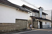 A walks her dog past Nakayu Sake Brewery in Kami Town, Miyagi Prefecture,  Japan on 02 Sept. 2012. Photographer: Robert Gilhooly