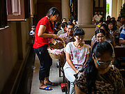 27 MARCH 2016 - BANGKOK, THAILAND: Students from Santa Cruz school hand out Easter eggs on Easter Sunday at Santa Cruz Church in Bangkok. Santa Cruz was one of the first Catholic churches established in Bangkok. It was built in the late 1700s by Portuguese soldiers allied with King Taksin the Great in his battles against the Burmese who invaded Thailand (then Siam). There are about 300,000 Catholics in Thailand, in 10 dioceses with 436 parishes. Easter marks the resurrection of Jesus after his crucifixion and is celebrated in Christian communities around the world.      PHOTO BY JACK KURTZ