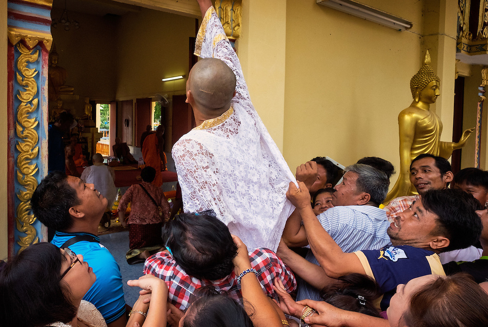 Thai Buddhist Monk Ordination in Nakhon Nayok, Thailand. Before the man who will be ordained enters the ordination hall, friends lift him up so he can touch the top of the doorway for luck and good fortune.