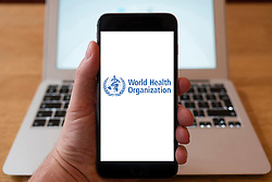 Using iPhone smartphone to display logo of World Health Organization, WHO