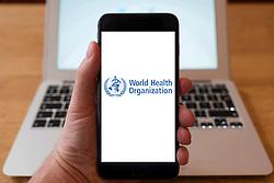 Using iPhone smartphone to display logo of World Health Organization, WHO