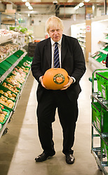 © Licensed to London News Pictures. 21/10/2011. London, UK. Mayor of London Boris Johnson hold a pumpkin during a tour of Waitrose's state of the art online distribution centre in Acton, West London today (21/10/2011). The centre delivers online order across the whole of London. Photo credit: Ben Cawthra/LNP