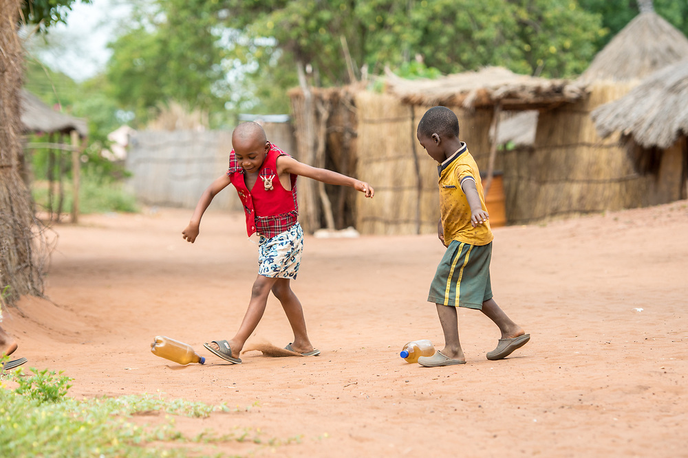 Two young Zambian boys kick along two bottles across the ground, Mukuni Village, Zambia