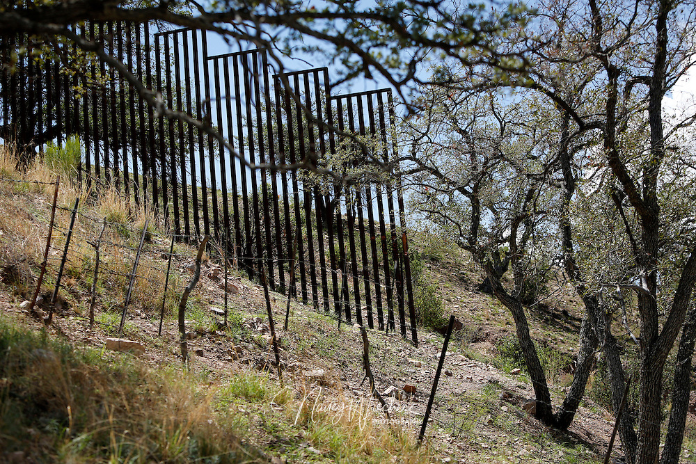 In a remote area west of Nogales, Ariz., steel-slat fencing along the Arizona-Mexico border ends. A more rudimentary barrier made of barbed wire can be seen in the foreground. When politicians talk about improving or adding fencing along the border, it's often this type of example they cite. Photo taken July 16, 2014. NANCY WIECHEC