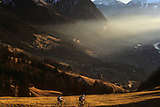 Looking downwards from a high vantage point on a hillside, we see one mountain-biker leading a second cyclist as they traverse across a sunlit mountainside near the hamlet of Masecha in the parish of Triesenberg, Liechtenstein. The late afternoon sun is low across the valley and there is a haze that partly obscures and refracts light over the distant landscape. There is snow on the distant mountain peaks but the countryside has the brown look of a snowless winter. Far off villages and hamlets hug the hillsides and golden light floods the scene. The tiny landlocked Principality of Liechtenstein is bordered by the Alpine countries of Austria and Switzerland and is a winter sports resort, though best known as a tax haven, attracting companies worldwide to register their assets in secrecy.  .