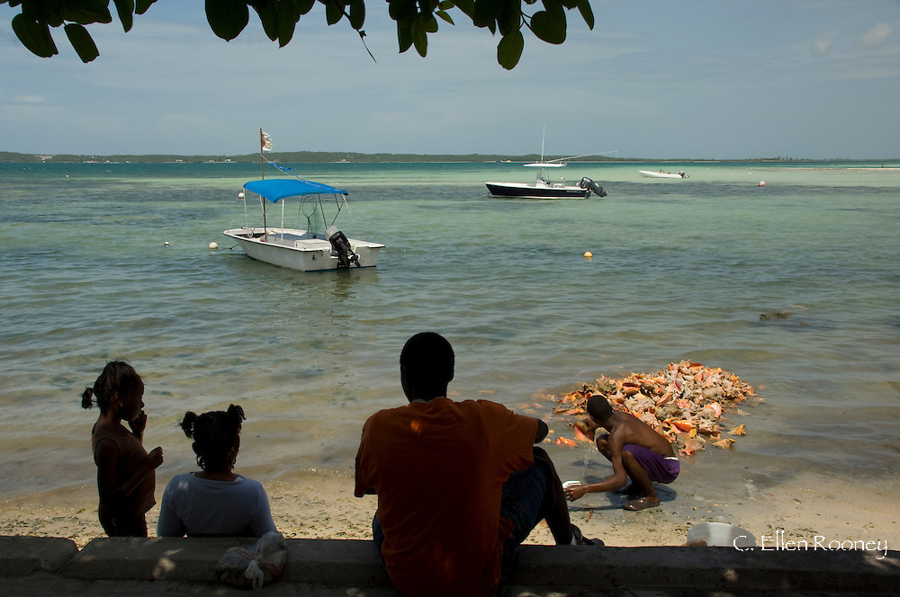 People watching a man cleaning conch shells in Dunmore Town, Harbour Island, The Bahamas