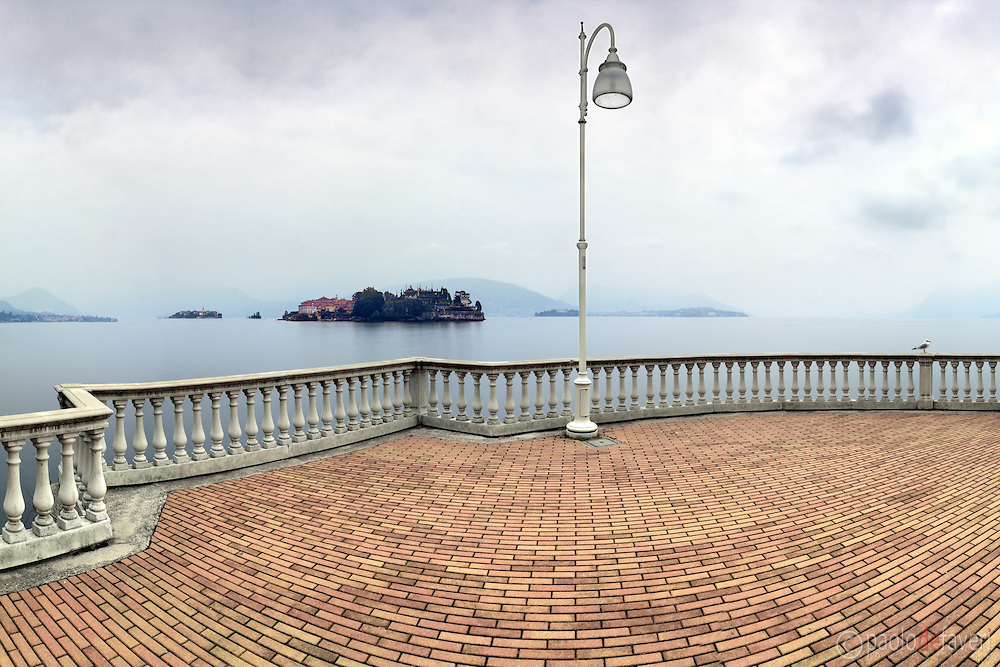 The terrace along the lake Maggiore in Stresa, Piedmont, Italy, on a cold and hazy autumn morning, with Isola Bella in the background.  Stitched from five vertical frames.