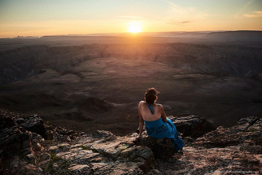 Eine Touristin geniesst den Sonnenuntergang   über der endlos weiten Landschaft an der Klippe des bis zu 550 Meter tiefen Schlucht des Fishriver Canyons.