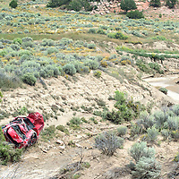 Lisa R. Benally's 2013 Chevy Impala lays at the base of an arroyo off Zuni Drive In road Wednesday. The car is over a mile from where it originally went off the road Sunday night during a rain storm.