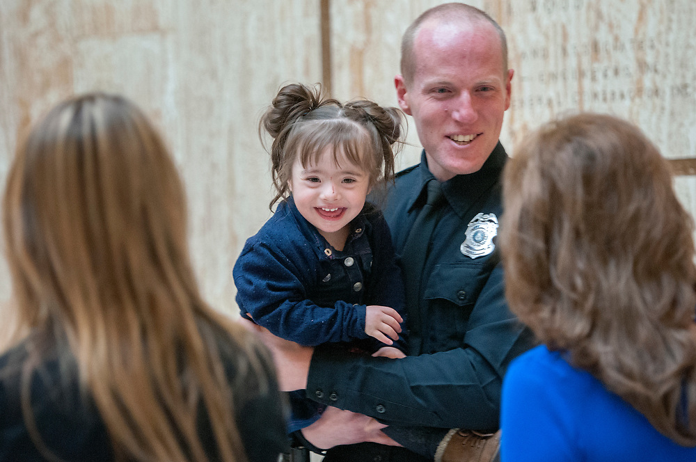 em020618c/a/APD Officer Ryan Holets holds Kaydence West Bera, 2, after a ceremony in the Rotunda of the State Capitol in Santa Fe Tuesday, February 6, 2018. Holets and his wife Rebecca have got national attention after they adopted a girl from a woman stuggling with a heroin addiction. Both were honored in the House Chambers as part of a memorial on New Mexico Angels on Earth Day. (Eddie Moore/Albuquerque Journal)