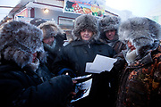 Salespeople on the Yakutsk outdoor fish market are looking to photographs I made two years ago of them and seem to be very happy to receive their promised photograph. Yakutsk (Russian: Яку́тск) is a city in the Russian Far East, located about 4° (450 kilometres) south of the Arctic Circle. It is the capital of the Sakha (Yakutia) Republic in Russia with a major port on the Lena River. The city has a population of 264.000 (2009). Yakutsk is one of the coldest cities on Earth. The average monthly winter temperature in January is around −43,2 °C. Yakutsk, Jakutsk, Yakutia, Russian Federation, Russia, RUS, 16.01.2010.