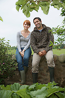 Couple sitting side by side on wall in countryside portrait