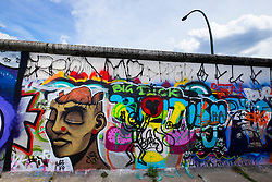 Graffiti on original section of Berlin Wall at East Side Gallery in Friedrichshain in Berlin Germany