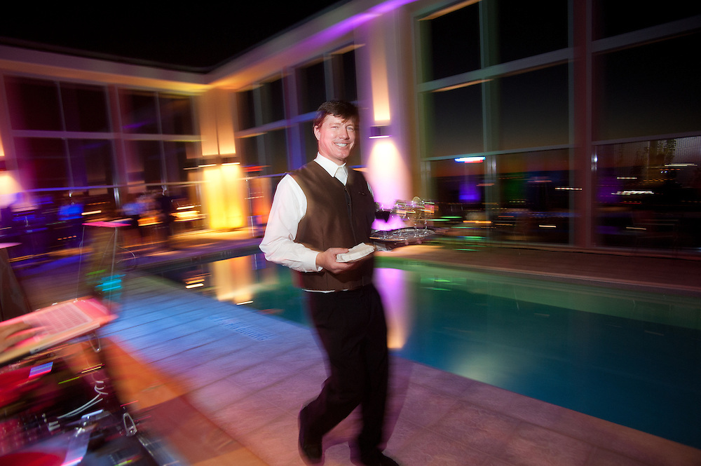 The Four Seasons Residences Austin hosted a party Friday night for current, future and prospective residents. A waiter delivers drinks to guests gathered at the pool.
