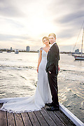 Bride and groom standing on a pier with the sunset behind them