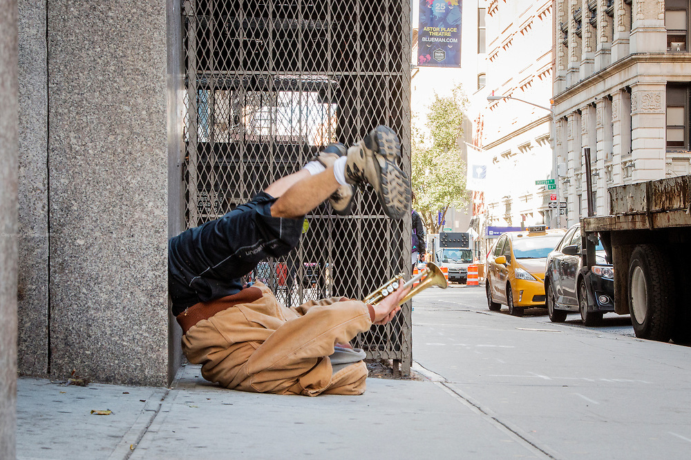 A man practices playing the trumpet upside down on Broadway and Great Jones.