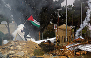 Tear gas and concausion grenades are thrown by the Israeli army towards a Palestinian demonstrator waving a Palestinian flag as he tries to cross a barrier blocking the