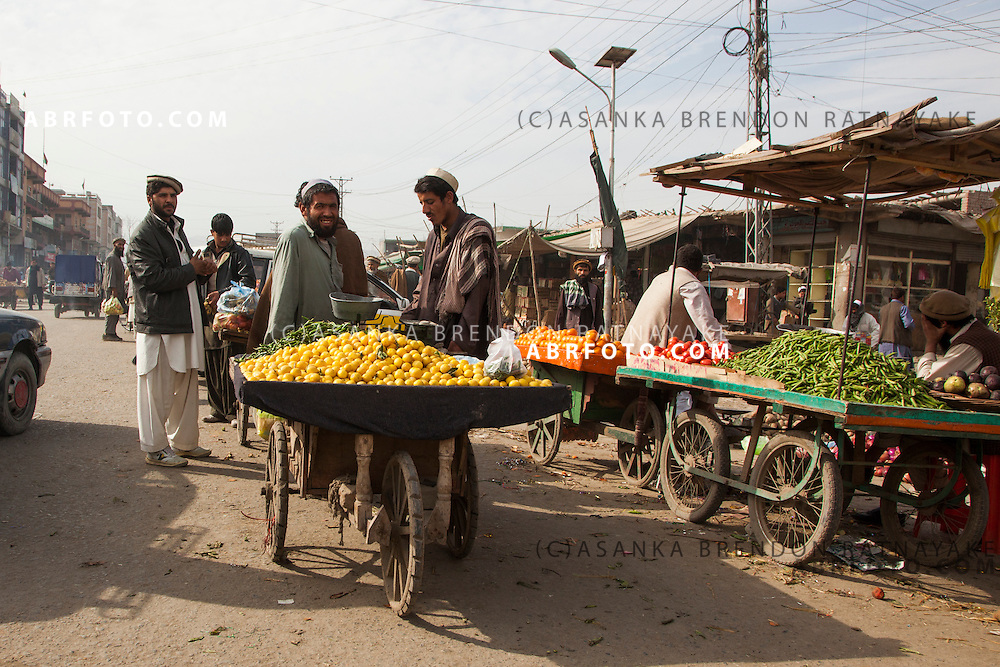 Men at a street side market selling lemons, tomatoes, chilli's on wooden carts.
