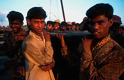 BANGLADESH CHITTAGONG MADHOM BIBIR HAT OCT00 - Labourers carry up to half-ton metal plates on their bare shoulders. Due to the heaviness of the plates, they chant rythmic songs to harmonise breathing and walking, a technique already applied by slave-gangs several centuries ago...Several thousand labourers work on one medium-sized (50,000 ton) ship for a period of around three months, until it is completely dismantled and taken apart. ..Since Bangladesh does not possess mineral resources such as iron ore, it works out more cost-efficient to employ a large army of day-labourers to recycle the scrapped ships rather than to import ore. On average, a labourer can expect to earn a little more than 1 US Dollar per day...jre/Photo by Jiri Rezac..© Jiri Rezac 2000..Contact: +44 (0) 7050 110 417.Mobile: +44 (0) 7801 337 683.Office: +44 (0) 20 8968 9635..Email: jiri@jirirezac.com.Web: www.jirirezac.com..© All images Jiri Rezac 2000 - All rights reserved.