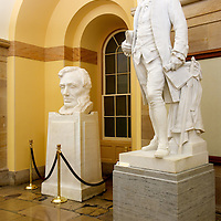 Marble statues of Abraham LIncoln and Caesar Rodney in the United States Capitol in Washington, DC.
