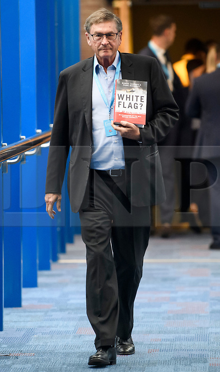 © Licensed to London News Pictures. 01/10/2018. Birmingham, UK. LORD MICHAEL ASHCROFT holds a copy of his book WHITE FLAG? As he attends day two of the 2018 Conservative Party autumn conference at the ICC in Birmingham. This years event is focused heavily on Brexit and negotiations with the EU over the UK's exit form the European Union. Photo credit: Ben Cawthra/LNP