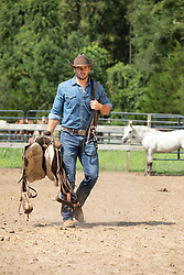 hot cowboy with a saddle on a ranch