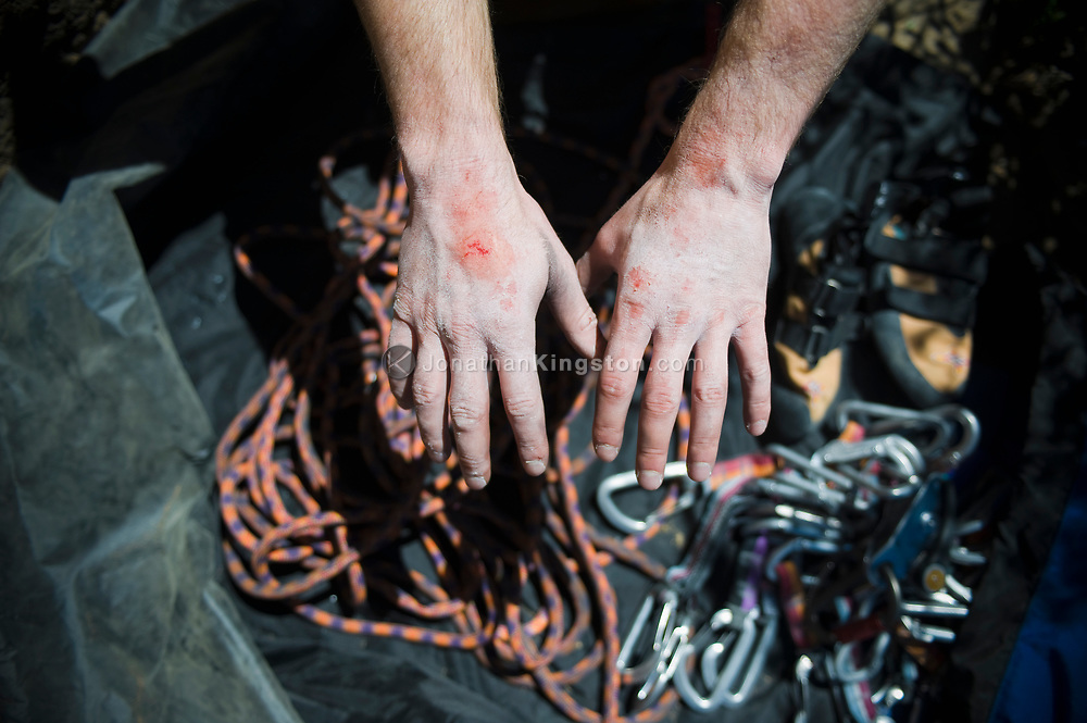 Chalk covered hands with climbing rope, shoes and carabiners in the background at Trout Creek, Oregon. (Model Released)