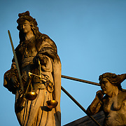 The early morning light catches a statue of Justice on top of the Provost's House (Proosdij), a historic baroque building dating to 1666 on Burg Square and standing opposite the gothic City Hall (Stadhuis) building. The Provost's House was used as the residence of the bishop of Bruges and now houses the government offices of West Flanders province.