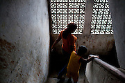 Razia Shabnam (in orange) goes down the stairs of her apartment with her son Saihaan, in Kidderpore, Calcutta, West Bengal, India as she leaves to referee an all-India invitational boxing competition in the neighbouring town of Burnpur. Razia Shabnam, 28, was one of the first women boxers in Kolkata. She was also the first woman in her community to go to college. She is now a coach and one of only three international female boxing referees in India. Photo by Suzanne Lee for Panos London