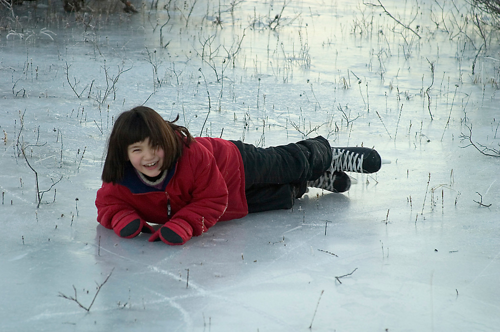 A girl laughs after falling on her ice skates.