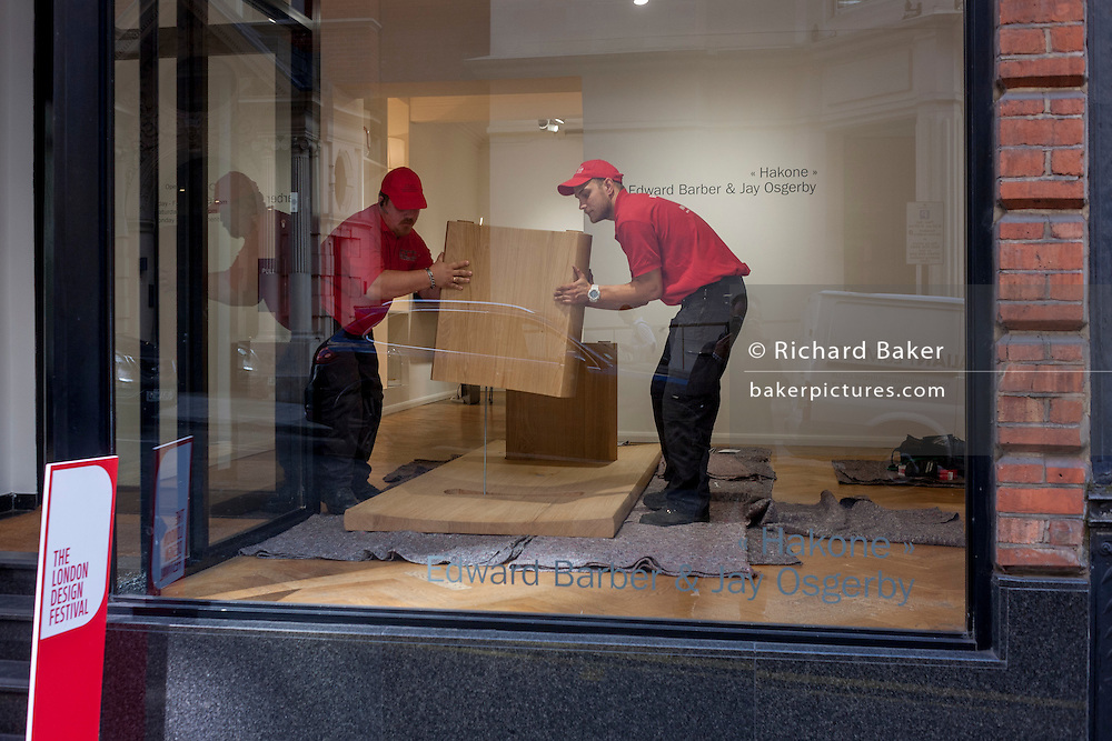 Two workmen carefully lift and place an exhibit, in the window of an art gallery in Mayfair, central London, England.