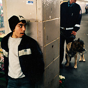 A young man stands away from a guard and his dog in Berlin's Kottbusser Tor metro station. ..Picture taken 2005 by Justin Jin