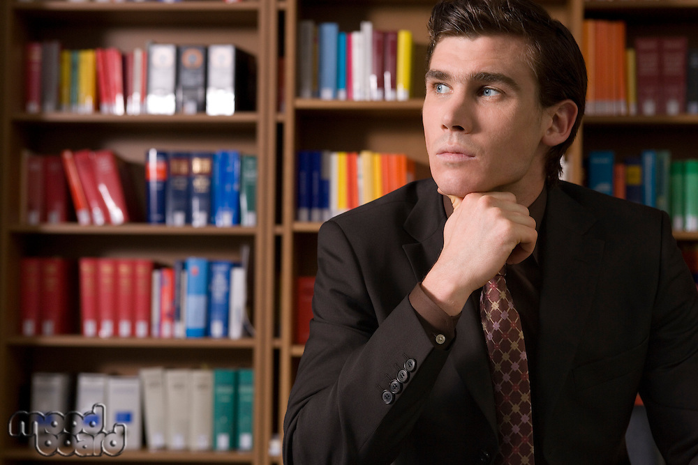 Pensive man wearing suit in library