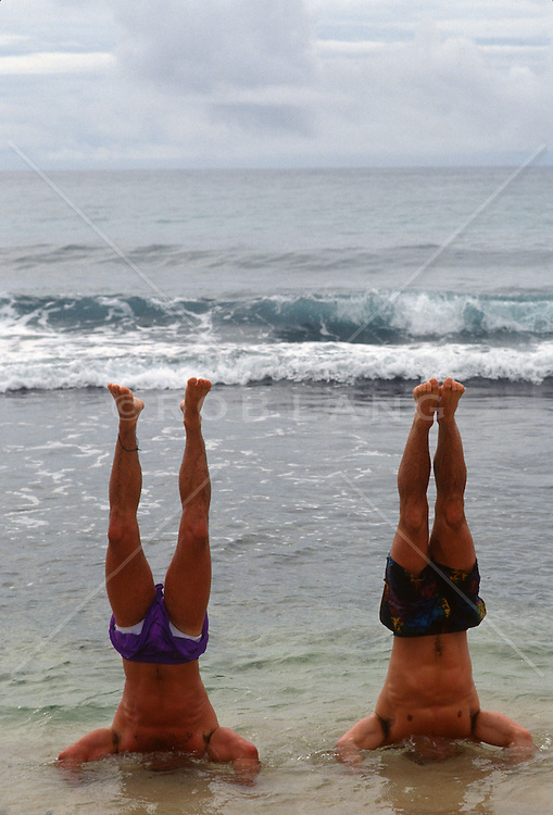 Two men in the ocean water doing handstands with their heads under the water