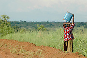 A strong African woman carries a bucket of water on her head. Uganda, Africa.