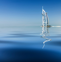 Luxury Burj al Arab Hotel reflected in the sea in Dubai United Arab Emirates UAE