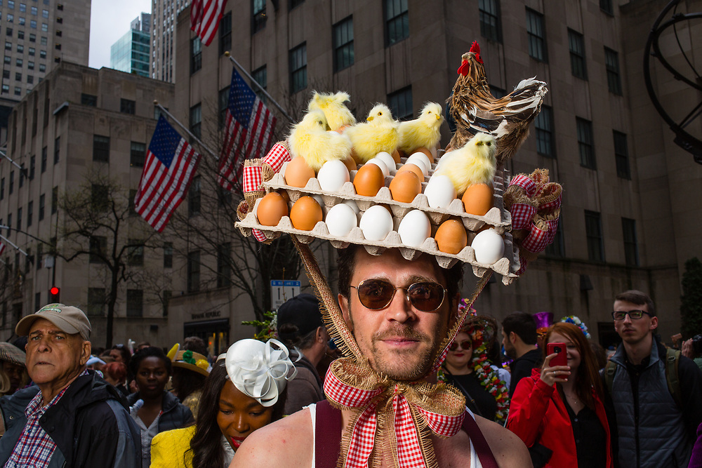 New York, NY - 21 April 2019. A man wears a hat bearing dozens of eggs, chicks, and a chicken at the Easter Bonnet Parade and Festival on New York's Fifth Avenue.