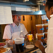 Chef Danny Bowien's restaurant, Mission Chinese, is photographed at its New York City location on the Lower East Side of Manhattan on Tuesday, July 31, 2012 in New York, NY. Bowien, left, talks with his co-workers before the start of the lunch shift. .