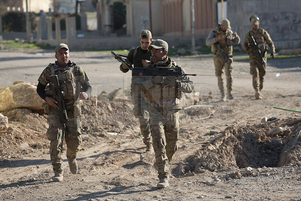 Licensed to London News Pictures. 20/02/2017. Albu Saif, Iraq. Soldiers of the Iraqi Emergency Response Division sprint across a street inside the village of Albu Saif as Iraqi Security Forces assault the settlement during the offensive to retake western Mosul from Islamic State forces.<br /> <br /> The settlement of Albu Saif is located on high ground overlooking Mosul Airport and as such is a strategic point that needs to be taken as part of the operation to retake the western side of Mosul. Photo credit: Matt Cetti-Roberts/LNP