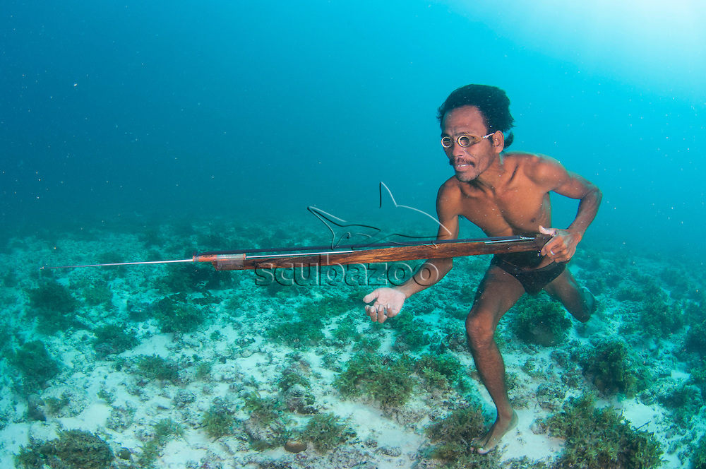Sulbin, a Bajau sea gypsy spearfisherman freediving and walking on the seabed hunting for fish with a homemade speargun, Mabul Island, Sabah, Malaysia.