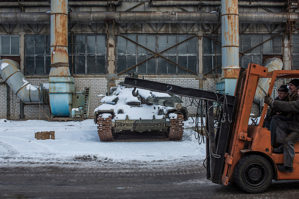 A forklift drives past a tank in for repair at the Malyshev Tank Factory on Wednesday, February 11, 2015 in Kharkiv, Ukraine.