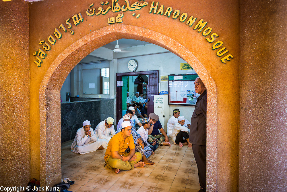 "08 AUGUST 2013 - BANGKOK, THAILAND:       Men pray in the entry way of Haroon Mosque during Eid al-Fitr in Bangkok. Eid al-Fitr is the ""festival of breaking of the fast,"" it's also called the Lesser Eid. It's an important religious holiday celebrated by Muslims worldwide that marks the end of Ramadan, the Islamic holy month of fasting. The religious Eid is a single day and Muslims are not permitted to fast that day. The holiday celebrates the conclusion of the 29 or 30 days of dawn-to-sunset fasting during the entire month of Ramadan. This is a day when Muslims around the world show a common goal of unity. The date for the start of any lunar Hijri month varies based on the observation of new moon by local religious authorities, so the exact day of celebration varies by locality.   PHOTO BY JACK KURTZ"