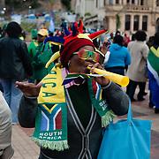 Zuid Afrikaanse vrouw blaast op een Vuvuzela tijdens het Wereldkampioenschap 2010 in Zuid Afrika